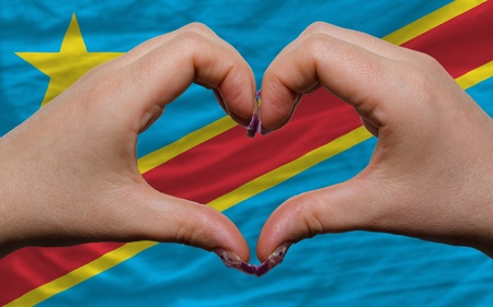 Gesture made by hands showing symbol of heart and love over flag of congo photo