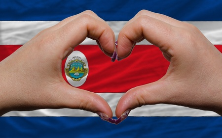 costa rican: Gesture made by hands showing symbol of heart and love over national costa rica flag