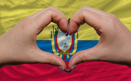 ecuadorian: Gesture made by hands showing symbol of heart and love over national ecuador flag