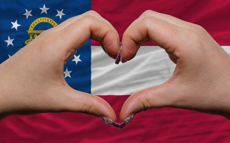 Gesture made by hands showing symbol of heart and love over us state flag of georgia photo
