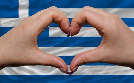 Gesture made by hands showing symbol of heart and love over national greece flag photo