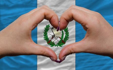 bandera de guatemala: Gesto de las manos que muestran el s�mbolo del coraz�n y el amor por la bandera nacional de Guatemala Foto de archivo