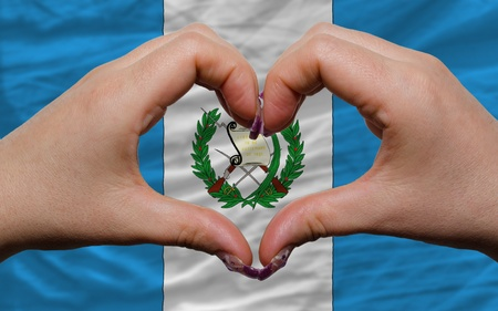guatemalan: Gesture made by hands showing symbol of heart and love over national guatemala flag Stock Photo