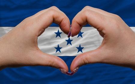 Gesture made by hands showing symbol of heart and love over national honduras flag photo