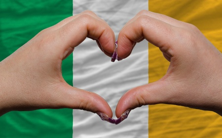 Gesture made by hands showing symbol of heart and love over national ireland flag photo