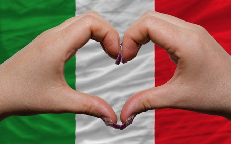 Gesture made by hands showing symbol of heart and love over national italy flag photo