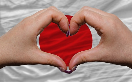 Gesture made by hands showing symbol of heart and love over national japan flag photo