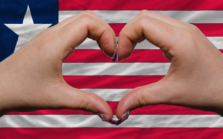 Gesture made by hands showing symbol of heart and love over national liberia flag photo