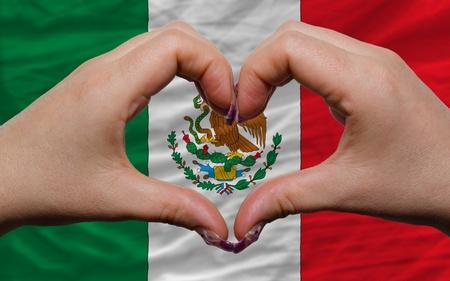 bandera mexicana: Gesto de las manos que muestran el s�mbolo del coraz�n y el amor por la bandera nacional de M�xico