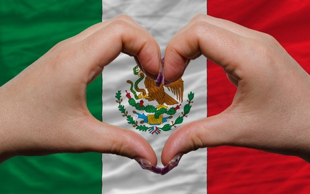 Gesture made by hands showing symbol of heart and love over national mexico flag photo