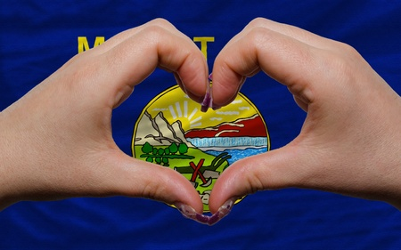 Gesture made by hands showing symbol of heart and love over us state flag of montana photo
