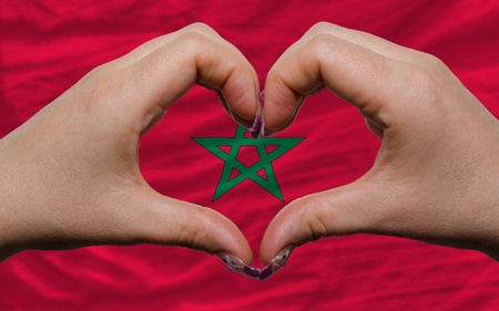 made in morocco: Gesture made by hands showing symbol of heart and love over national morocco flag