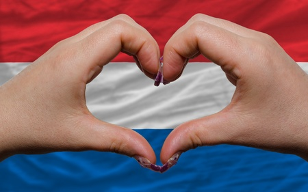 Gesture made by hands showing symbol of heart and love over national netherlands flag photo