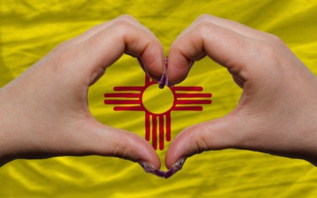 Gesture made by hands showing symbol of heart and love over us state flag of new mexico photo