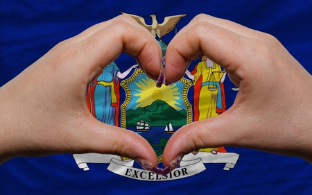 Gesture made by hands showing symbol of heart and love over us state flag of new york photo