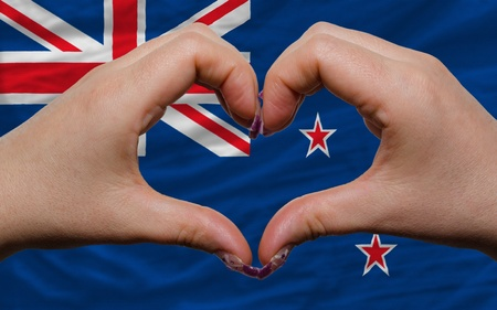 Gesture made by hands showing symbol of heart and love over national new zealand flag photo