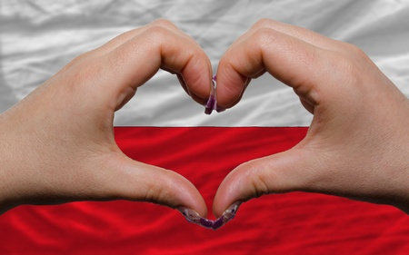 Gesture made by hands showing symbol of heart and love over national poland flag photo