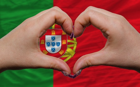 Gesture made by hands showing symbol of heart and love over national portugal flag photo