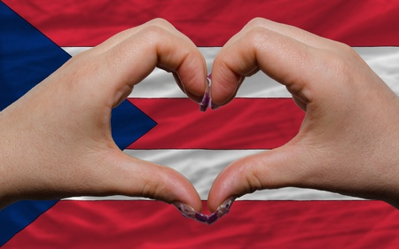 puerto rican flag: Gesture made by hands showing symbol of heart and love over national puertorico flag Stock Photo