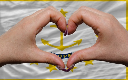 Gesture made by hands showing symbol of heart and love over us state flag of rhode island photo