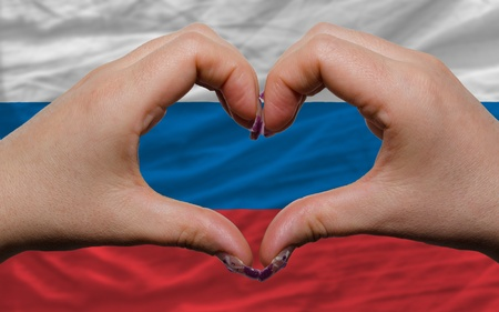Gesture made by hands showing symbol of heart and love over national russia flag photo
