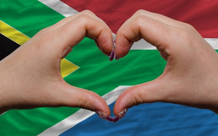 Gesture made by hands showing symbol of heart and love over national south africa flag photo