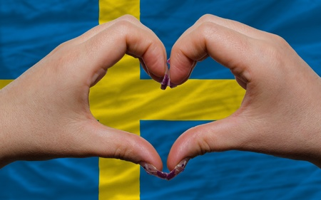 Gesture made by hands showing symbol of heart and love over national sweden flag photo