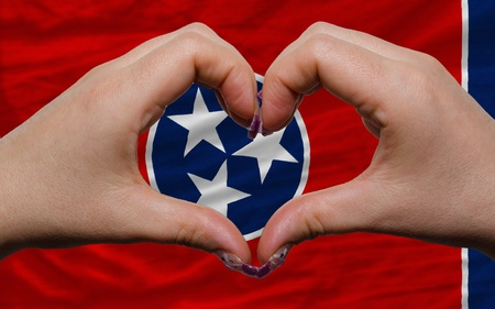 Gesture made by hands showing symbol of heart and love over us state flag of tennessee photo