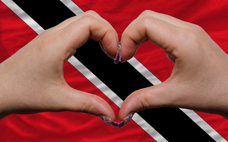 national flag trinidad and tobago: Gesture made by hands showing symbol of heart and love over national trinidad tobago flag