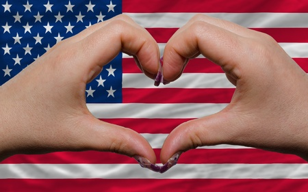 Gesture made by hands showing symbol of heart and love over national america flag photo