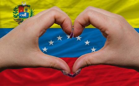 bandera de venezuela: Gesto de las manos que muestran el s�mbolo del coraz�n y el amor por la bandera nacional de Venezuela