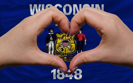 wisconsin flag: Gesture made by hands showing symbol of heart and love over us state flag of wisconsin