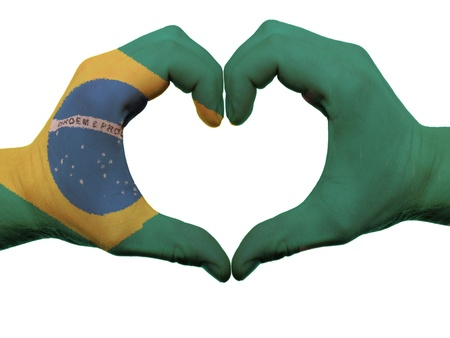 Gesture made by brazil flag colored hands showing symbol of heart and love, isolated on white background