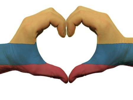 Gesture made by colombia flag colored hands showing symbol of heart and love, isolated on white background Фото со стока