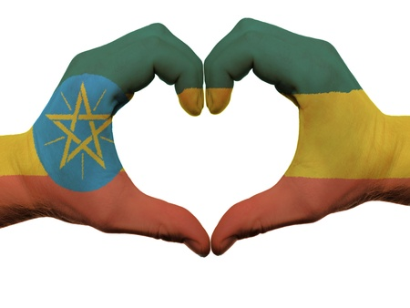 Gesture made by ethiopia flag colored hands showing symbol of heart and love, isolated on white background photo