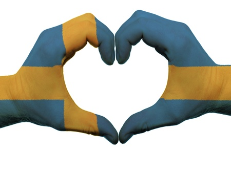 Gesture made by sweden flag colored hands showing symbol of heart and love, isolated on white background photo