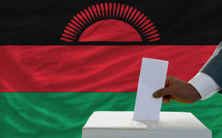 malawian flag: man putting ballot in a box during elections  in front of national flag of malawi