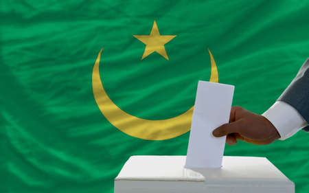 man putting ballot in a box during elections  in front of national flag of mauritania photo