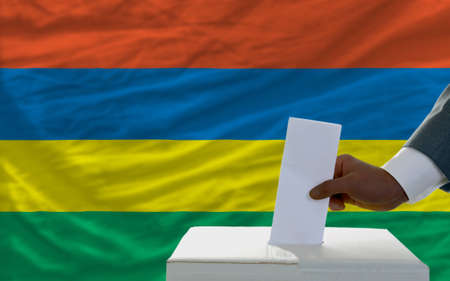 man putting ballot in a box during elections  in front of national flag of mauritius photo