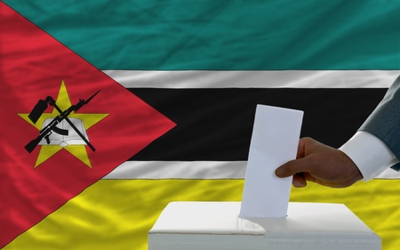 man putting ballot in a box during elections  in front of national flag of mozambique photo