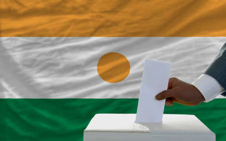 man putting ballot in a box during elections  in front of national flag of niger photo