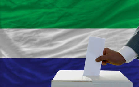 man putting ballot in a box during elections  in front of national flag of sierra leone photo