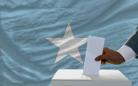 somali: man putting ballot in a box during elections  in front of national flag of somalia
