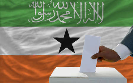 man putting ballot in a box during elections  in front of national flag of somaliland photo