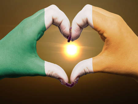 Gesture made by ireland flag colored hands showing symbol of heart and love during sunrise photo