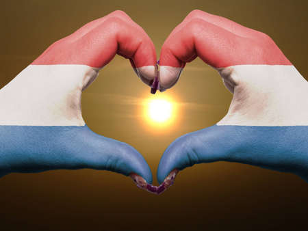 made in netherlands: Gesture made by netherlands flag colored hands showing symbol of heart and love during sunrise