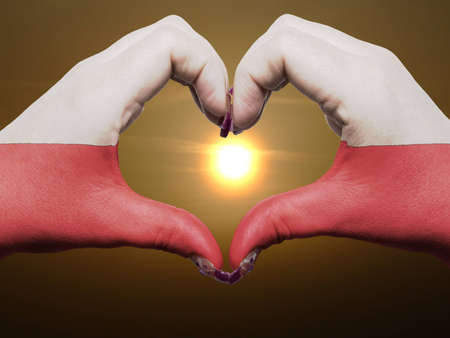 Gesture made by poland flag colored hands showing symbol of heart and love during sunrise photo