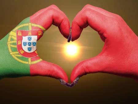 drapeau portugal: Geste effectu� par les mains Drapeau Portugal en couleurs montrant le symbole du c?ur et de l'amour au lever du jour