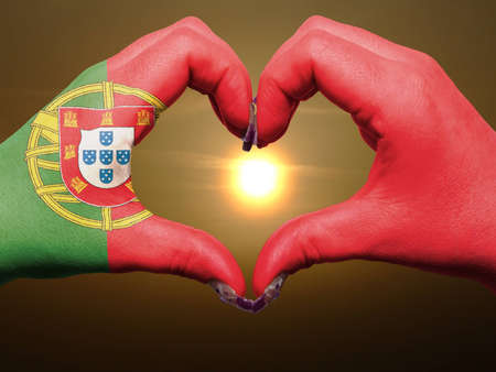 made in portugal: Gesture made by portugal flag colored hands showing symbol of heart and love during sunrise Stock Photo