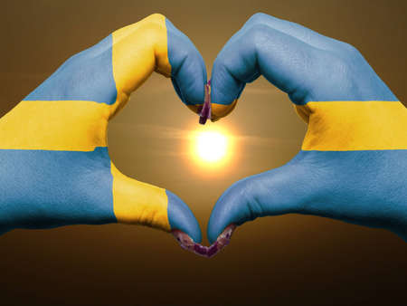 Gesture made by sweden flag colored hands showing symbol of heart and love during sunrise photo
